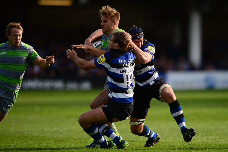 BATH, ENGLAND - SEPTEMBER 23: Chris Harris of Newcastle Falcons is tackled by Max Clark of Bath Rugby and Paul Grant of Bath Rugby during the Aviva Premiership match between Bath Rugby and Newcastle Falcons at the Recreation Ground on September 23, 2017 in Bath, England. (Photo by Harry Trump/Getty Images)